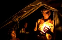 child_holds_candle_outside_his_tent
